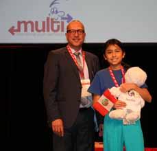 Bild: Kulturdezernent Apostolos Tsalastras übergab der jüngsten Multi-Teilnehmerin, der elfjährigen Mayra aus Peru, ein kleines Willkommensgeschenk. (Foto: Stadt Oberhausen)