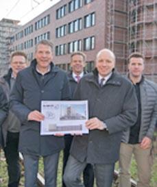 Bild: Stehen vor der neuen Fassade des EVO-Gebäudes, v.li.: Frank Mols und Bernd Homberg (EVO), Wolfgang Schepers und Oliver Mebus (Stadtsparkasse) sowie Architekt Moritz Ebbers. (Foto: Oliver T. Müller)