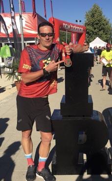 Bild:                                         Feuerwehrmann Sven Storm präsentiert hier stolz seine Triathlon-Medaille. (Foto: Feuerwehr)