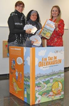 Bild: Die KIM-Mitarbeiterinnen Natascha Beulshausen (li.) und Fatma Kurt-Ayar (Mitte) sowie Eva Rogge (evo) mit dem aktuellen Wimmelbuch. (Foto:evo)